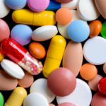 Different colorful pills and drugs background. Medicinal tablets, capsules and pills. Top view